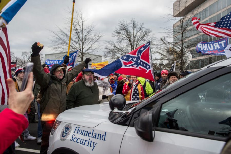 Trump+supporters+surround+a+police+car+during+riots+of+the+Capitol+Building+on+January+6.