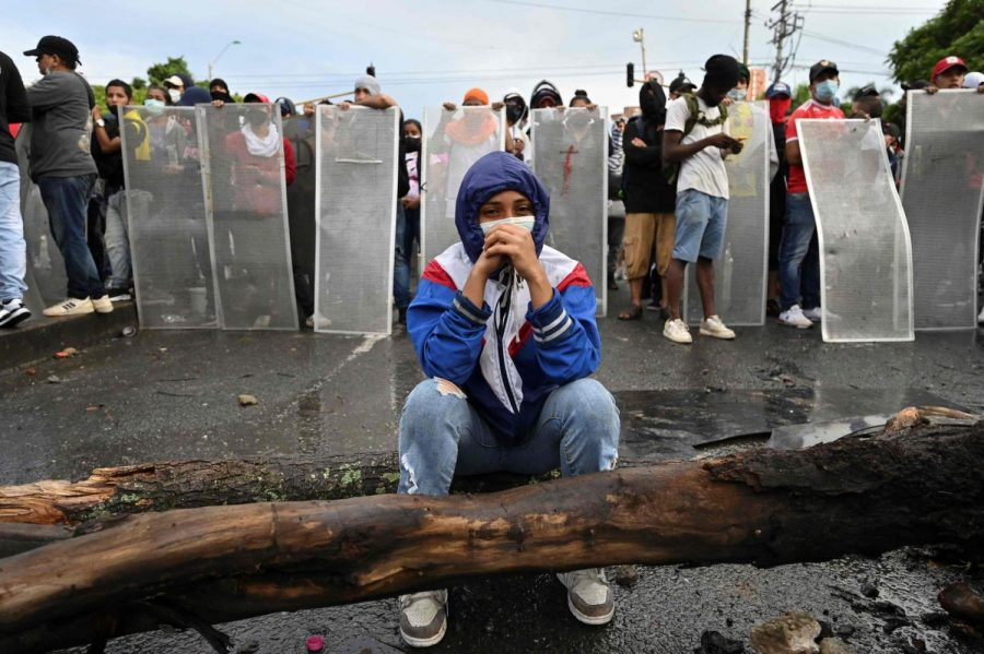 A protestor sits as demonstrators stand behind makeshift shields during clashes with riot police officers in Cali, Colombia