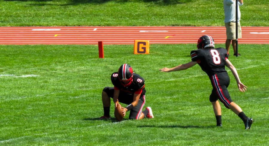 Junior AJ Rivera holds the ball for sophomore Ryan Smidt as he attempts (a successful) extra point.